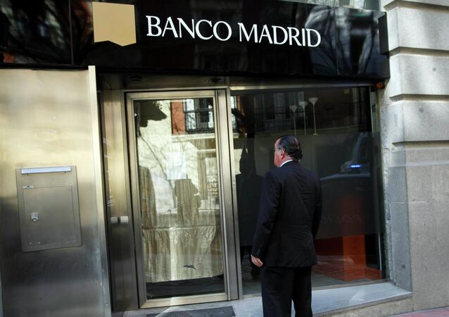 A man stands in front of the entrance of a closed Banco Madrid branch in Madrid, March 16, 2015