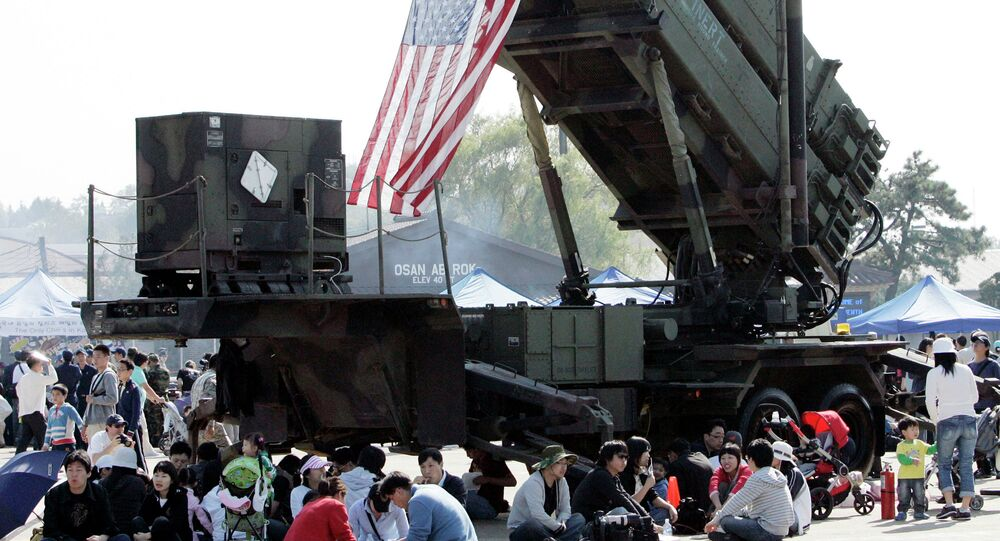 South Korean visitors shelter from the sun under the shadow of a U.S. Surface-to Air missile Patriot launcher during Air Power Day at the U.S. airbase in Osan, south of Seoul, South Korea