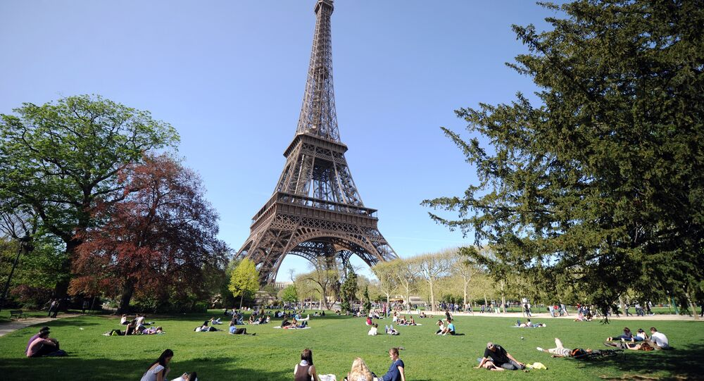 People enjoy the sunny spring weather near the Eiffel tower in Paris