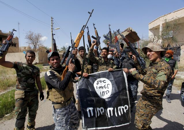 Iraqi security forces and Shi'ite paramilitary fighters hold an Islamist State flag, which they pulled down in Tikrit, March 31, 2015.