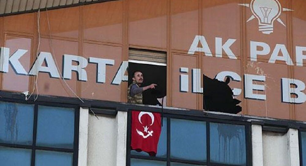 One of the two gunmen displays Turkish flag after smashing window at AK Party office in İstanbu