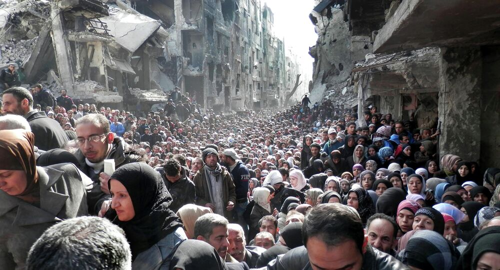 Residents of the besieged Palestinian camp of Yarmouk, queue to receive food supplies, Syria