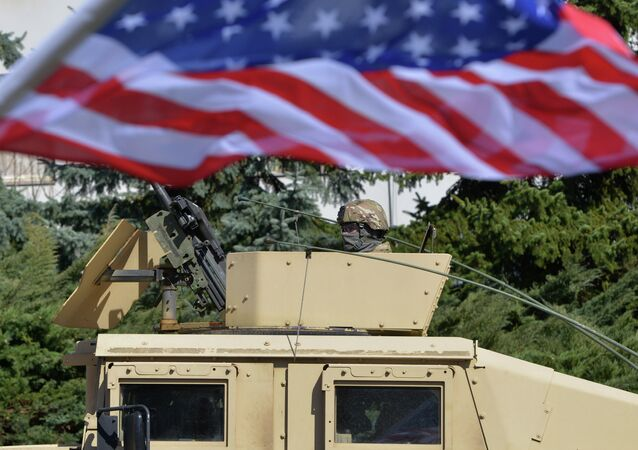 A US soldier looks from the armored vehicle Humvee