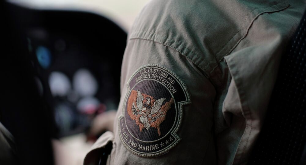 A US Customs and Border Protection Air and Marine agent's patch is seen as he patrols patrol near the Texas-Mexico border.