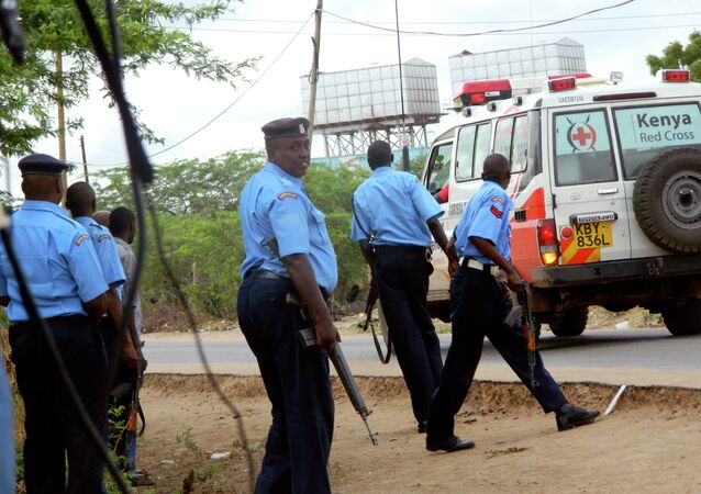 Kenyan police officers take positions outside the Garissa University College as an ambulance carrying the injured going to a hospital, during an attack by gunmen in Garissa, Kenya, Thursday, April 2, 2015.
