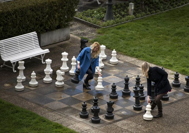 Russian journalists play a game of giant chess in a courtyard of the Beau Rivage Palace Hotel in Lausanne, Switzerland