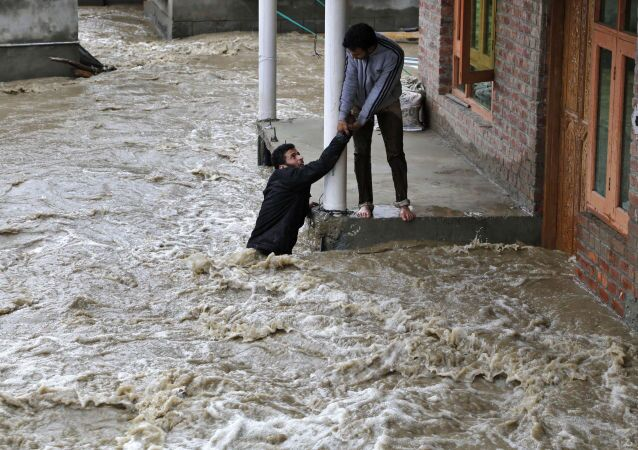 A Kashmiri man stretches his hand to help a local evacuate from a flood affected area in Srinagar, Indian-controlled Kashmir