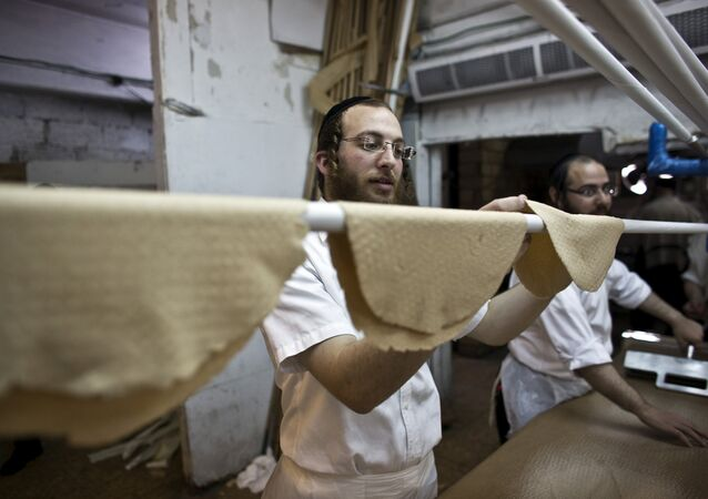 An ultra-Orthodox Jewish man places kneaded dough on a stick before it is placed in the oven to prepare matza, the traditional unleavened bread eaten during the Jewish holiday of Passover, in Bnei Brak near Tel Aviv