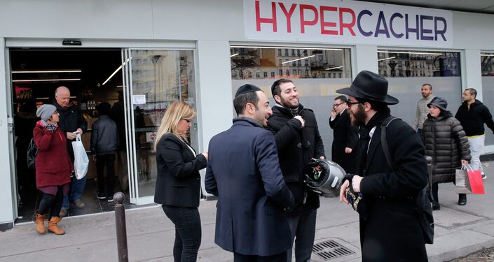Customers chat in front of the Hyper Cacher during its reopening, in Paris, France, Sunday, March 15, 2015.
