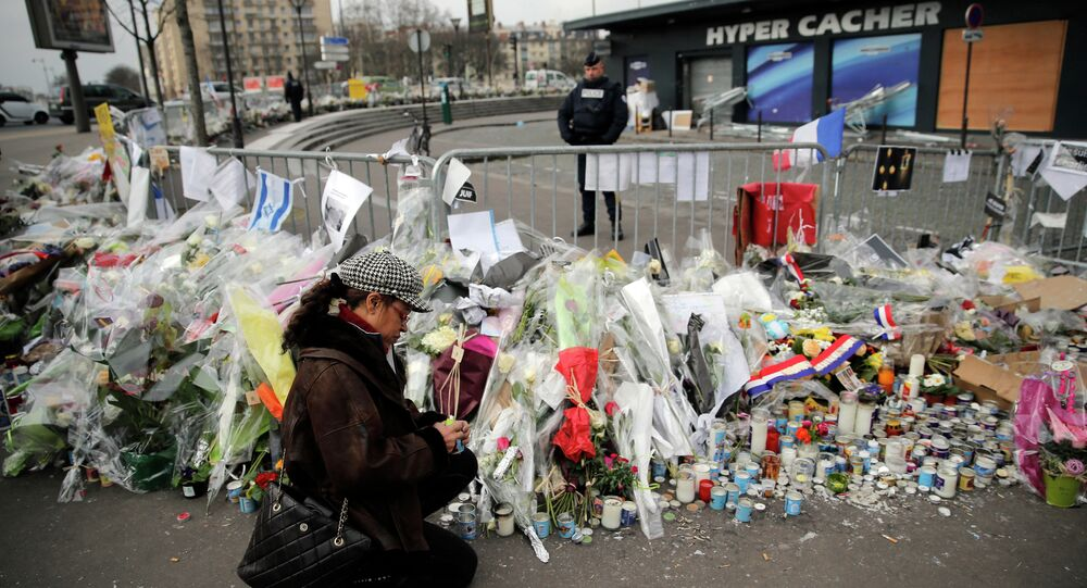 A woman lighting a candle outside the kosher grocery where Amedy Coulibaly killed four people in a terror attack, in Paris, France.