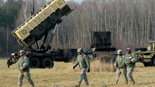 U.S soldiers walk next to a Patriot missile defence battery during join exercises at the military grouds in Sochaczew, near Warsaw - Sputnik International