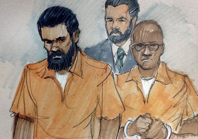 In this courtroom sketch, Jonas M. Edmonds(L) and Hasan R. Edmonds(R) stand in front of an FBI agent as they appear at a hearing at federal court in Chicago, Thursday, March 26, 2015, following their arrests Wednesday on charges of conspiring with the Islamic State group