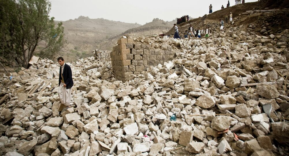 Yemenis stand amid the rubble of houses destroyed by Saudi-led airstrikes in a village near Sanaa, Yemen, Saturday, April 4, 2015