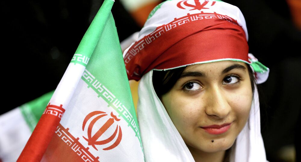 Iranian woman holds an Iranian flag during a ceremony