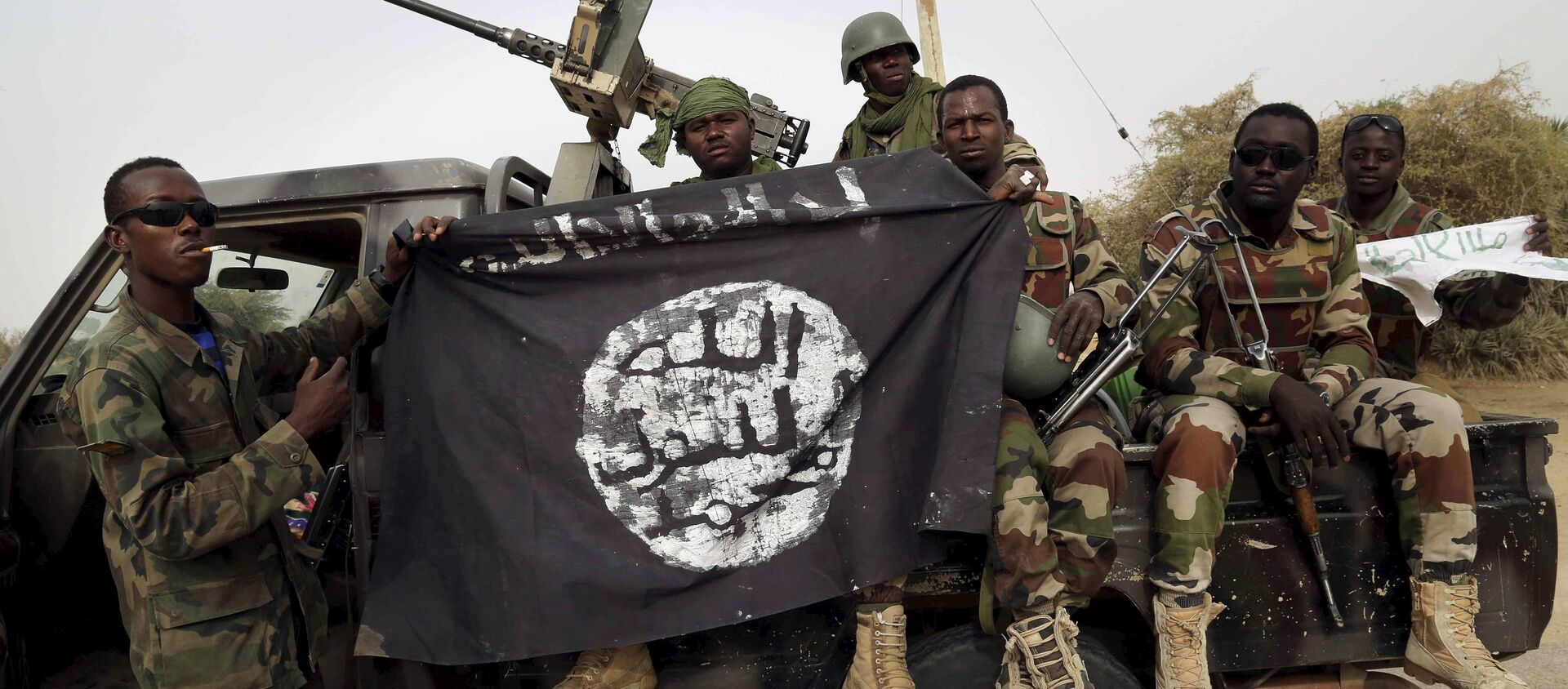 Nigerien soldiers hold up a Boko Haram flag that they had seized in the recently retaken town of Damasak, Nigeria, March 18, 2015 - Sputnik International, 1920, 24.07.2021