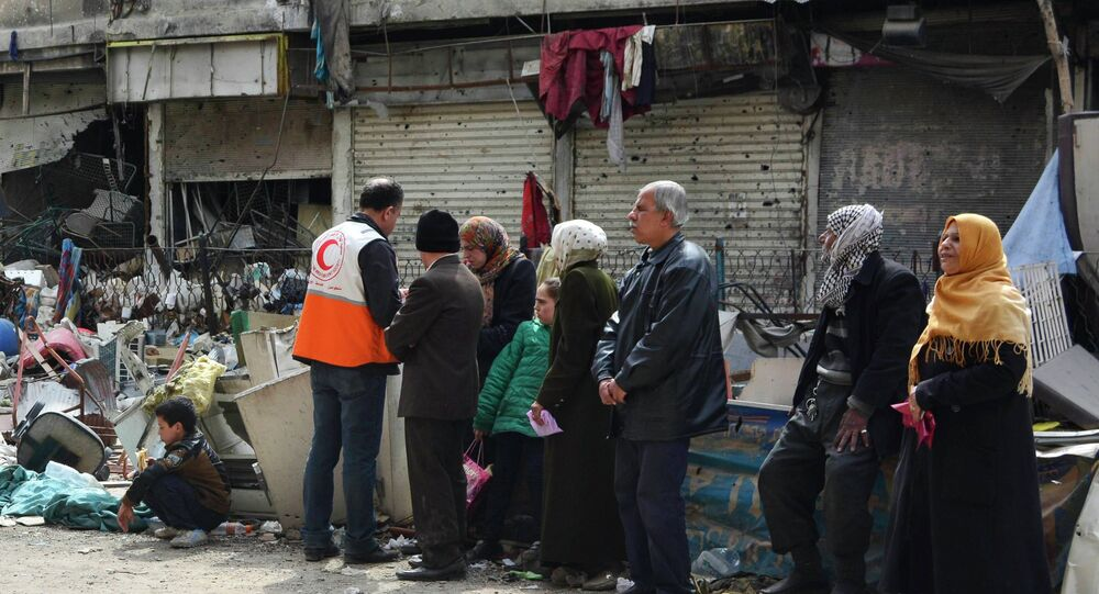 Residents wait to receive humanitarian aid at the Palestinian refugee camp of Yarmouk, in Damascus March 11, 2015