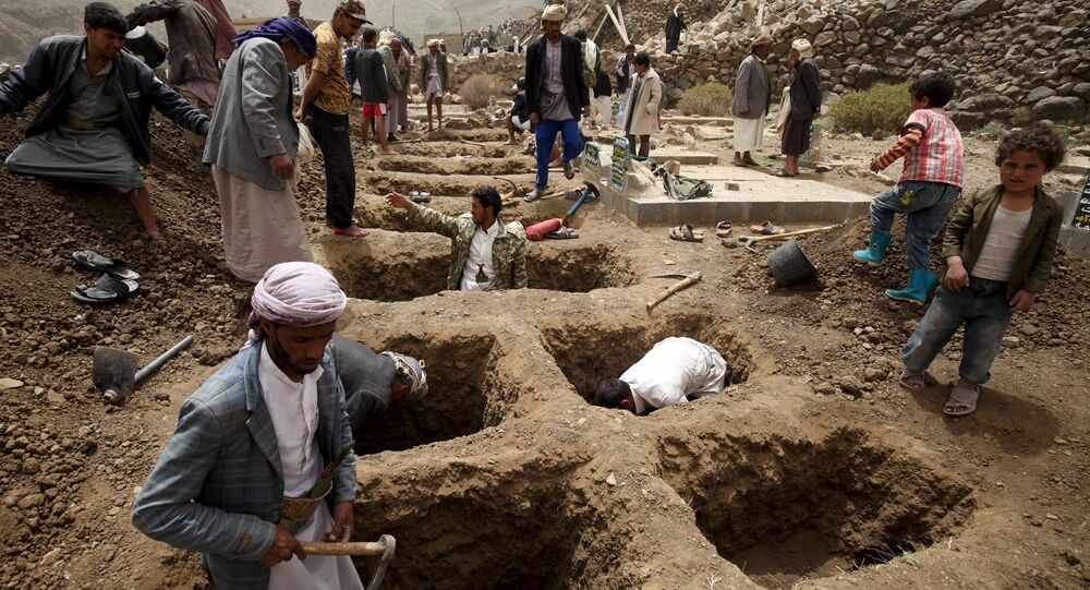 People dig graves for the victims of an air strike in Okash village near Sanaa April 4, 2015