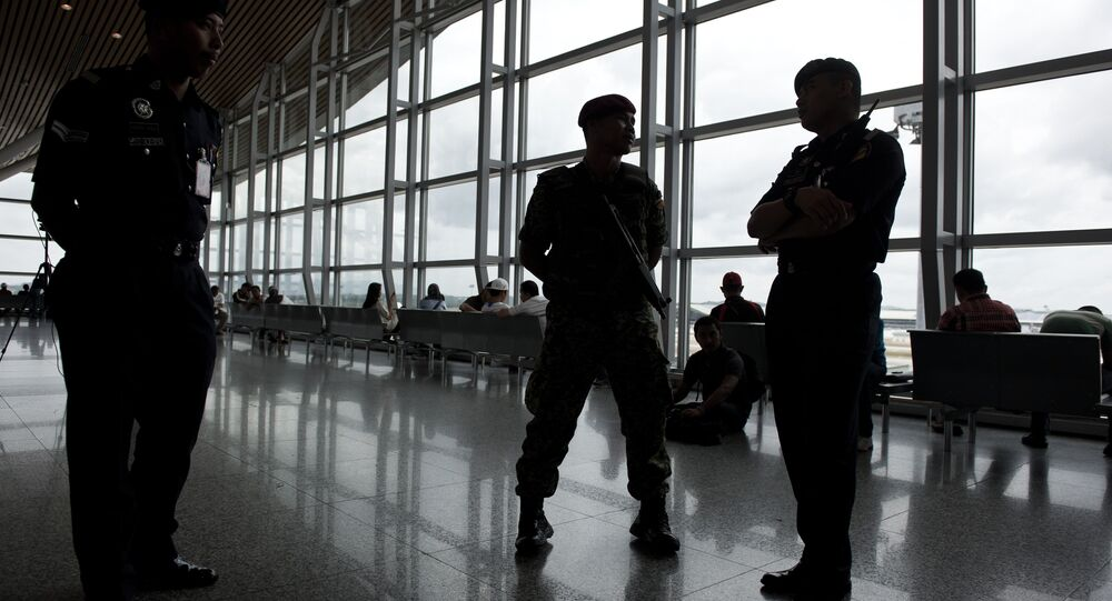 A member of the Malaysian Army (C) and a Malaysian policemen are silhouetted as they stand guard at Kuala Lumpur International Airport (KLIA) in Sepang, outside Kuala Lumpur on March 16, 2014