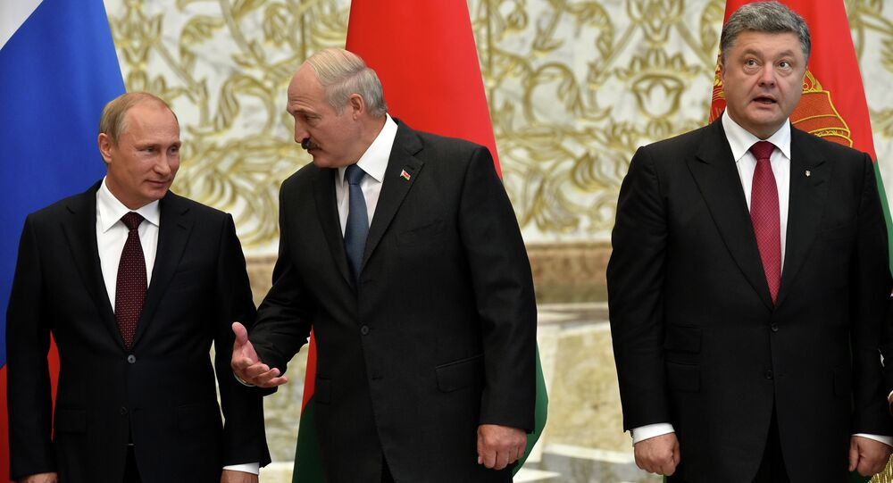 Belarus' President Alexander Lukashenko (C) gestures next to Russia's President Vladimir Putin (L) and Ukraine's President Petro Poroshenko as they meet in the Belarussian capital Minsk