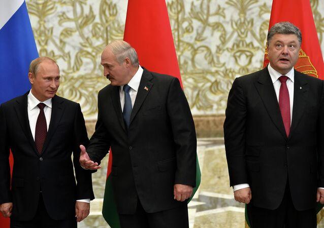 Belarus' President Alexander Lukashenko (C) gestures next to Russia's President Vladimir Putin (L) and Ukraine's President Petro Poroshenko as they meet in the Belarussian capital Minsk