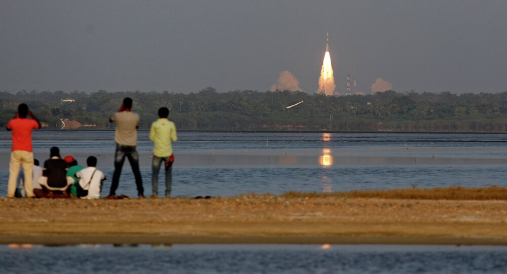 People watch the PSLV-C27 take off carrying India's fourth navigational satellite, in Sriharikota, India, Saturday, March 28, 2015