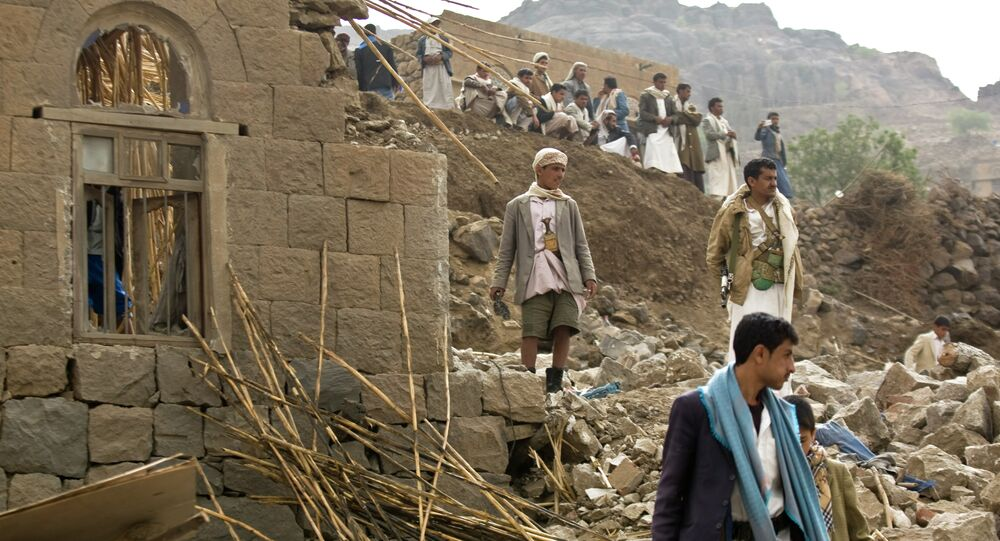 In this Saturday, April 4, 2015 file photo, Yemenis stand amid the rubble of houses destroyed by Saudi-led airstrikes in a village near Sanaa, Yemen