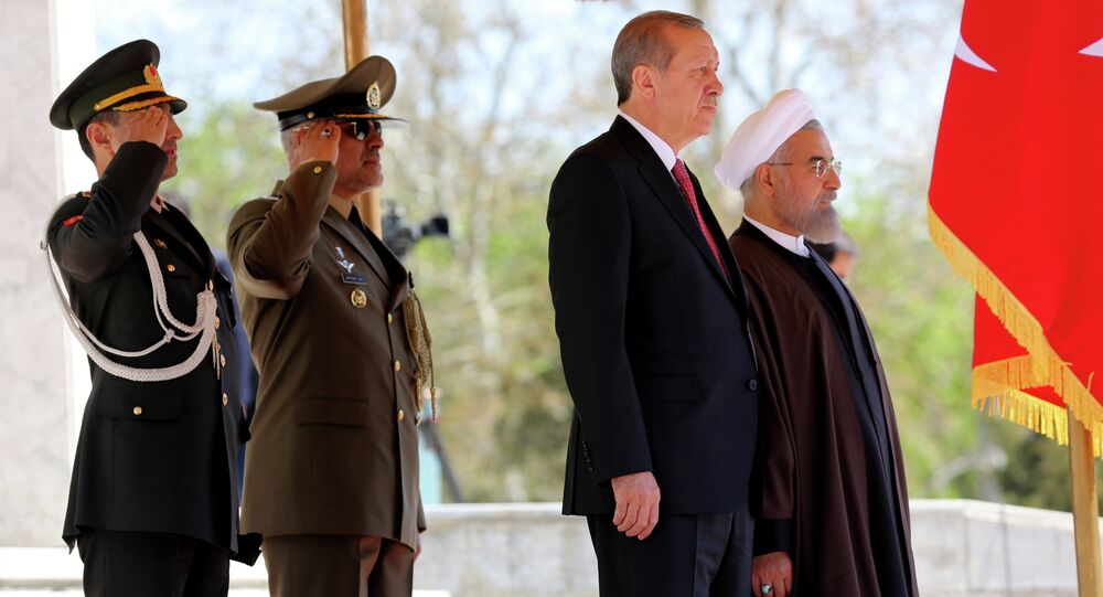 Iran's President Hassan Rouhani (R) stands with Turkish President Recep Tayyip Erdogan (2R) during an official welcoming ceremony following the latter's arrival at the Saadabad Palace in Tehran on April 7, 2015