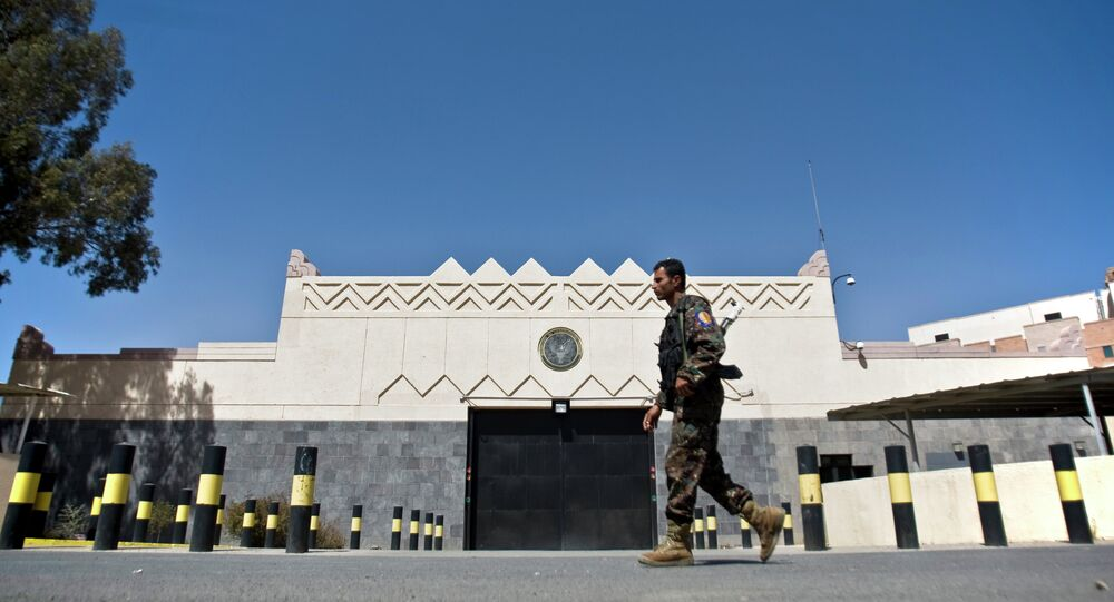 A Houthi fighter wearing an army uniform, walks past the gate of the main entrance of the US embassy after Yemeni police opened the road in front of it in Sanaa, Yemen, Wednesday, March 4, 2015