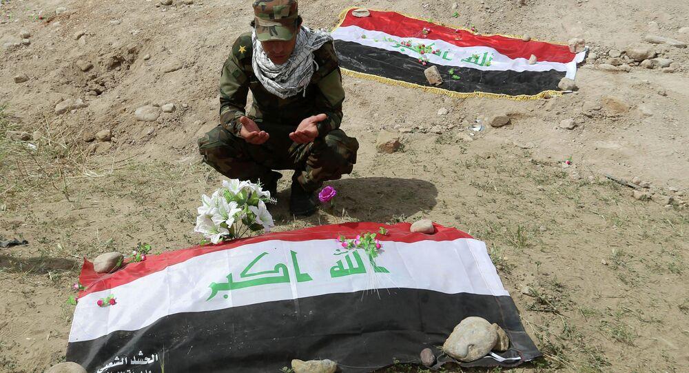 Shiite militiaman prays at a mass grave