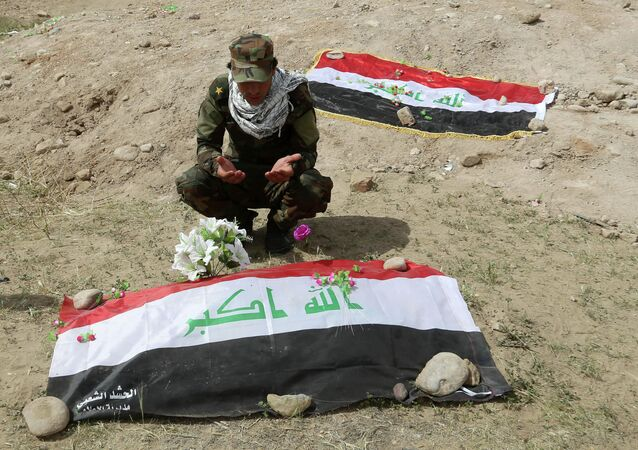 Shiite militiaman prays at a mass grave