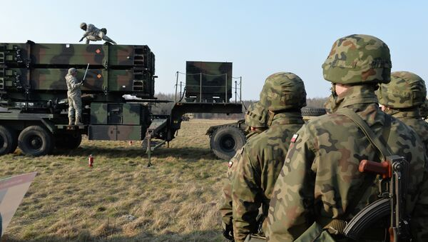 Polish soldiers watch as US troops from the 5th Battalion of the 7th Air Defense Regiment emplace a launching station of the Patriot air and missile defence system at a test range in Sochaczew, Poland. - Sputnik International