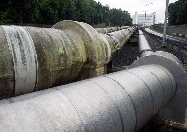 Transfer pipes carry liquified natural gas to and from a holding tank, seen in background, at Dominion Energy's Cove Point LNG Terminal in Lusby, Md., Thursday, June 12, 2014