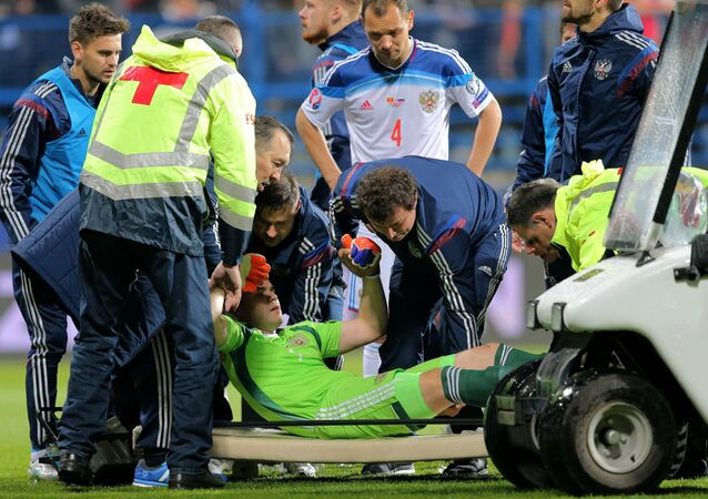 Medics evacuate Russian goalie Igor Akinfeyev from the pitch who was traumatized during the UEFA EURO 2016 qualifying match between the national teams of Montenegro and Russia