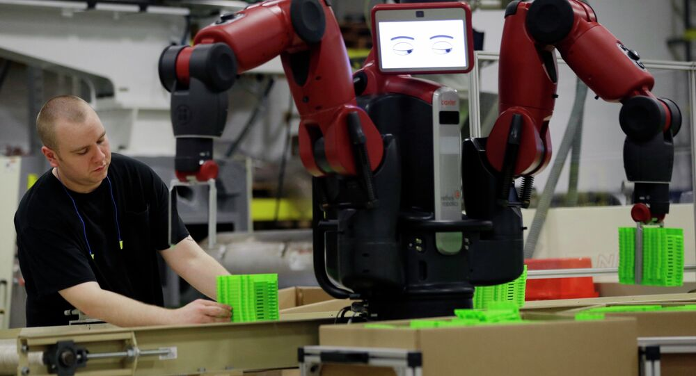 A technician works with Baxter, an adaptive manufacturing robot created by Rethink Robotics at The Rodon Group manufacturing facility, Tuesday, March 12, 2013, in Hatfield, Pa.