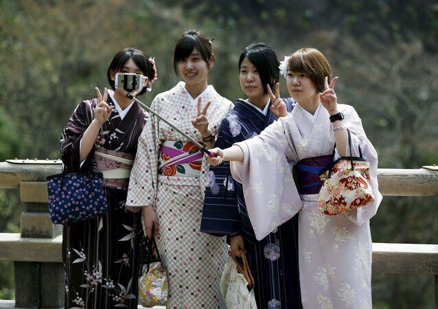 Kimono-clad women take selfies by using a selfie stick at Kiyomizu-dera Buddhist temple in Kyoto, western Japan