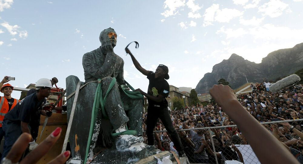 A student beats the statue of Cecil John Rhodes with a belt as it is removed from the University of Cape Town (UCT), April 9, 2015