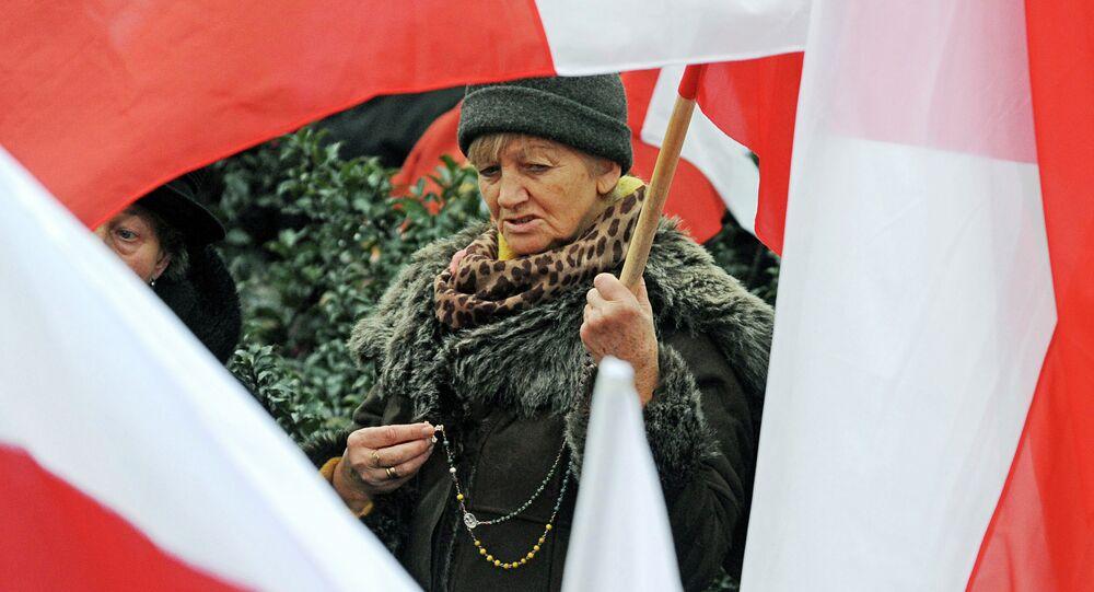 A woman seen between Polish national flags