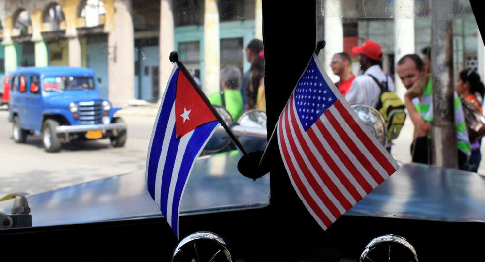 Miniature flags representing Cuba and the United States are displayed on the dash of an American classic car in Havana, Cuba.