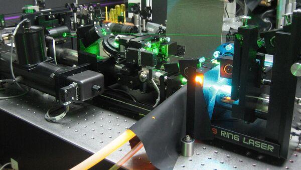 A Rhodamine laser dye (fluorescing orange) pumped with several Watts of Argon-ion laser radiation (bright blue) - Sputnik International