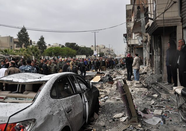 Syrian residents and security forces inspect the damage following a car bomb explosion on April 10, 2015, in the government-controlled majority Alawite neighbourhood of Hay al-Arman, located on the outskirts of the Zahraa district in Homs city