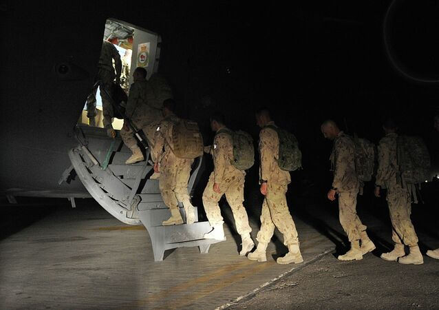 Canadian soldiers walk to board a plane on their way home at Kandahar airbase
