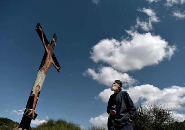 A monk of the Greek Orthodox Church looks at an image of Jesus crucified during the ceremony marking the Apokathelosis, the removal of Christ's dead body from the Cross, which forms a key part of Orthodox Easter, in a ceremony at the Church of the Dormition of the Virgin in Penteli, north Athens