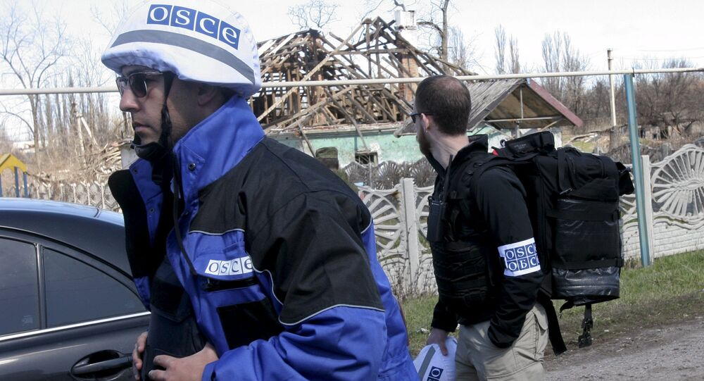 Members of the Special Monitoring Mission of the Organization for Security and Cooperation (OSCE) to Ukraine walk past a house damaged by shelling, in the village of Spartak outside Donetsk April 10, 2015