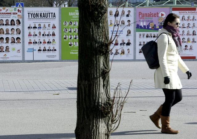 A woman walks past campaign posters of candidates in the Finnish Parliamentary elections put up along a street in Helsinki, April 10, 2015