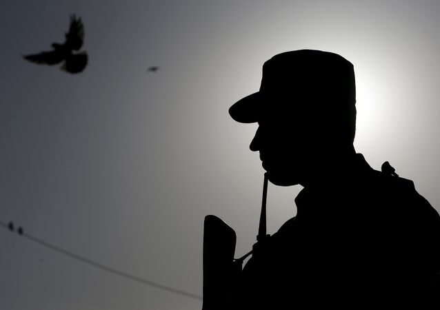 An Afghan policeman stands guard during a protest by Islamic clerics to condemn the killing of Farkhunda, in Kabul