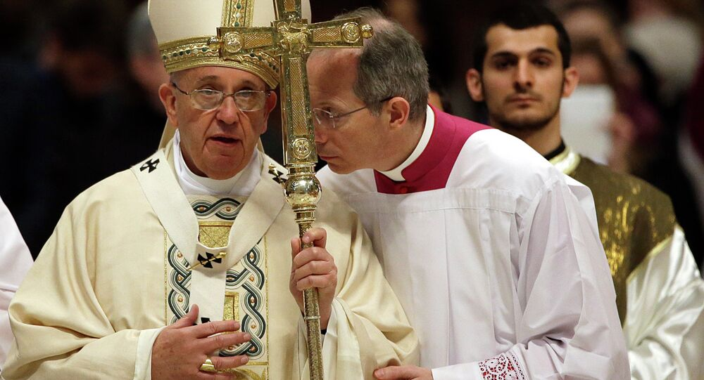 Monsignor Guido Marini, center, shares a word with Pope Francis, left, at the end of an Armenian-Rite Mass to commemorate the 100th anniversary of the Armenian Genocide, in St. Peter's Basilica, at the Vatican, Sunday, April 12, 2015.