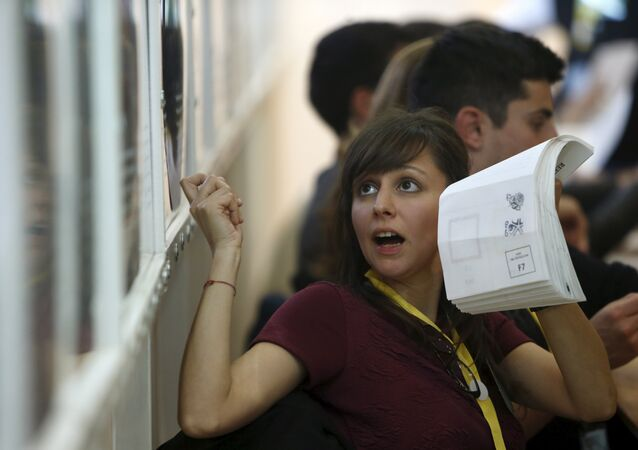 A counting staff member shows ballot papers to counting agents during the vote sorting in a referendum on spring hunting at the Vote Counting Complex in Naxxar, outside Valletta, April 12, 2015.