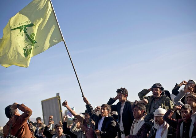 A Houthi Shiite Yemeni holding a flag of Hezbollah, center, chants slogans during a rally to show support for their comrades in Sanaa, Yemen