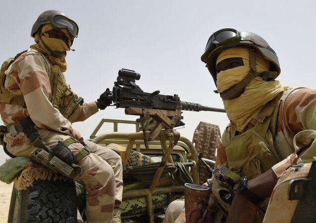 Nigerien army forces sit in the back of an armed pickup truck