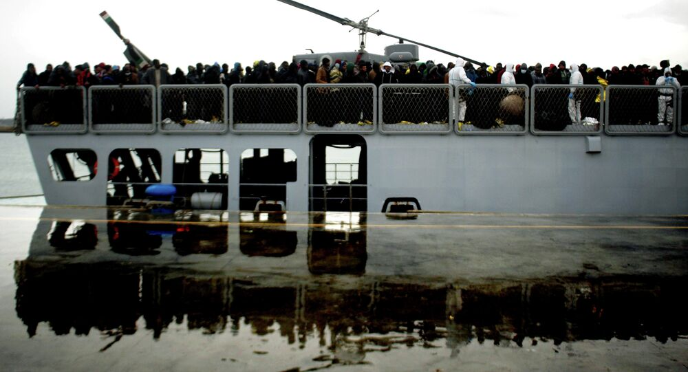 Migrants wait to disembark from a ship on February 17, 2015 in the port of Porto Empedocle, south Sicily, following a rescue operation of migrants as part of the International Frontex plan